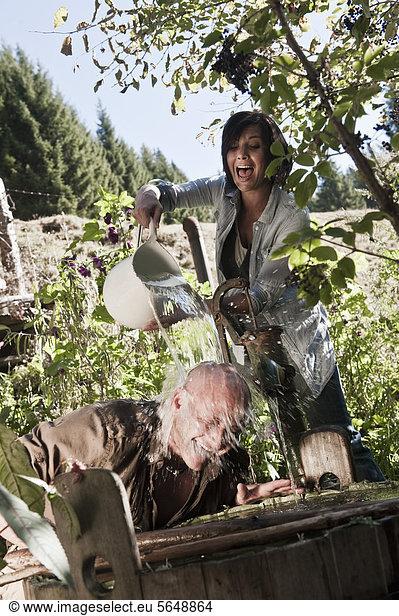 Austria,  Salzburg,  Flachau,  Woman pouring water on man head