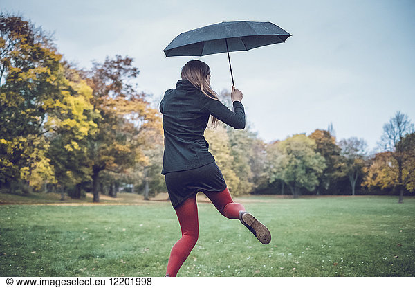 Back view of young woman with umbrella dancing in autumnal park