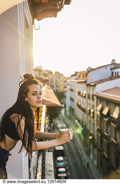 Beautiful young woman on balcony above the city at sunset with cup of coffee