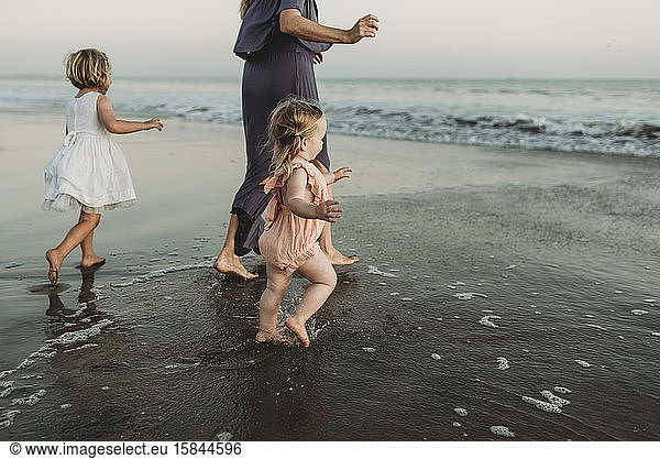 Behind view of young family walking towards the ocean at sunset, Behind view of young family walking towards the ocean at sunset