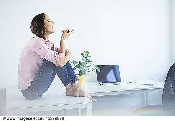 Cheerful young woman sitting on desk and talking on phone