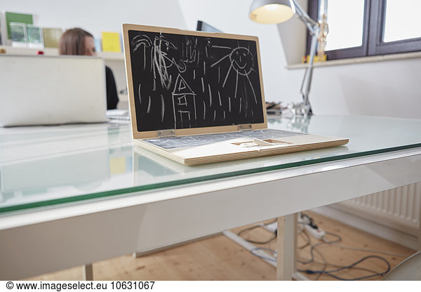 Children's toy notebook with chalk drawing on a desk