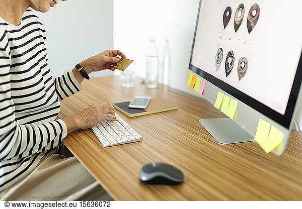 Close-up of woman using desktop pc for online shopping at home