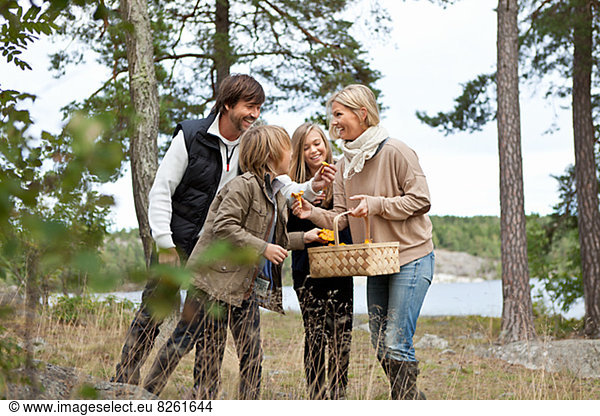 Family with two kids picking mushrooms
