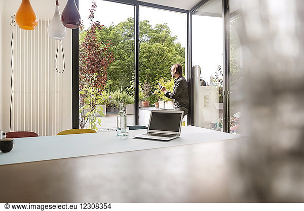 Germany,  businessman using tablet on balcony,  laptop on table