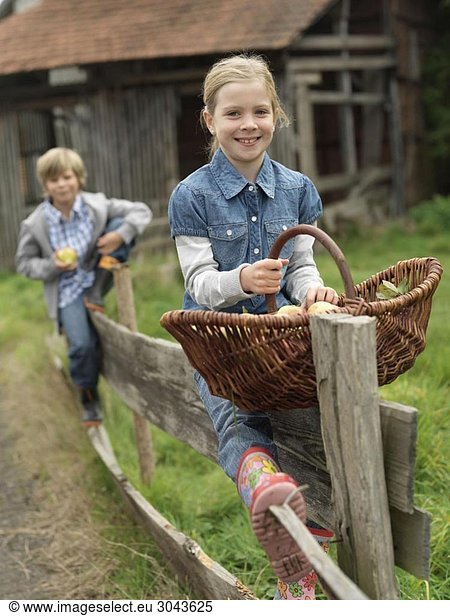 Girl and boy on fence with apples