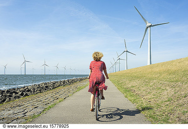 Girl cycling between onshore and offshore wind farm,  Urk,  Flevoland,  Netherlands, Girl cycling between onshore and offshore wind farm,  Urk,  Flevoland,  Netherlands