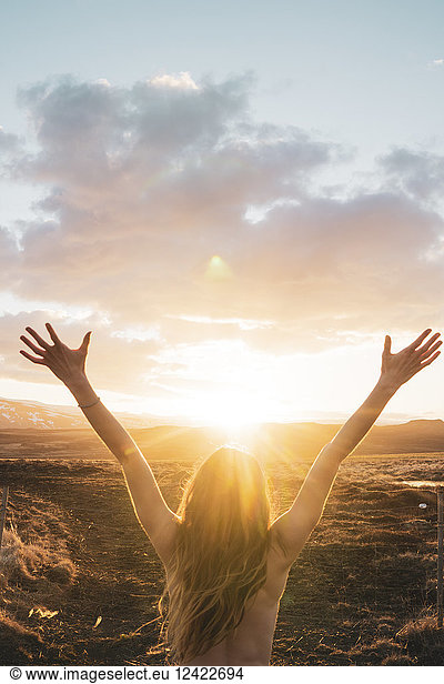 Iceland,  young woman with raised arms at sunset, Iceland,  young woman with raised arms at sunset