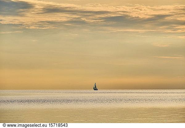 Italy,  Trentino,  Nago-Torbole,  Silhouette of sailboat sailing across Lake Garda at moody dawn, Italy,  Trentino,  Nago-Torbole,  Silhouette of sailboat sailing across Lake Garda at moody dawn