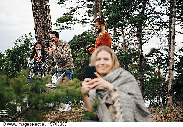 Male and female friends using smart phones while resting at forest