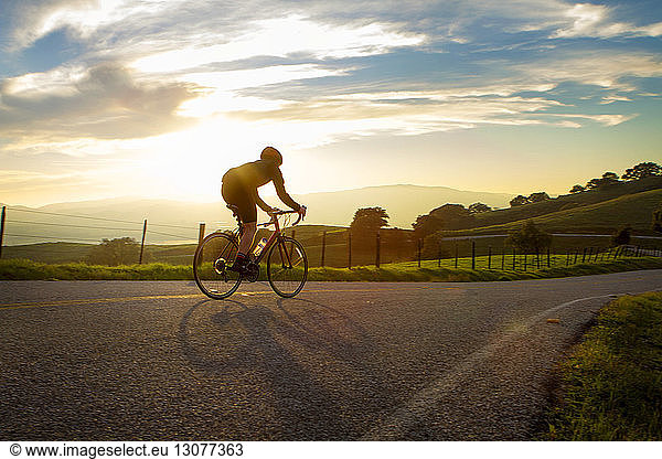 Man cycling on street against cloudy sky