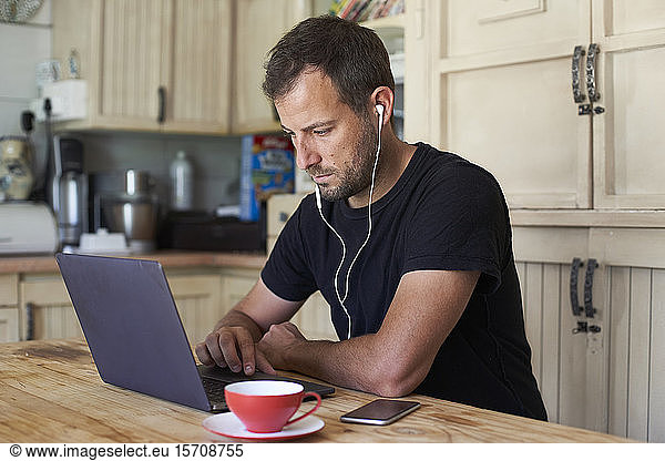 Man working from home,  sitting at kitchen table,  using laptop and smartphone