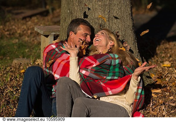 Mature couple sitting against tree trunk throwing autumn leaves at night