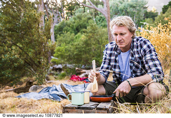 Mature man frying breakfast on camping stove in forest,  Deer Park,  Cape Town,  South Africa