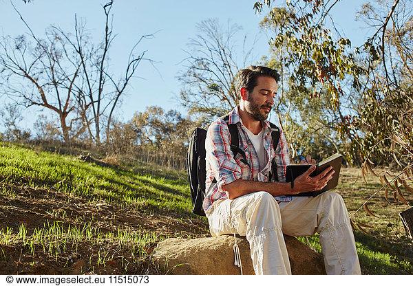 Mid adult man hiking,  sitting on boulder reading book