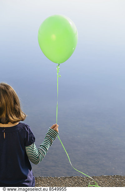 Nine year old girl holding green balloon,  sitting by waters edge, Nine year old girl holding green balloon,  sitting by waters edge