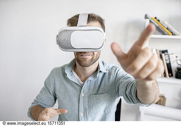 Portrait of man wearing VR glasses in office