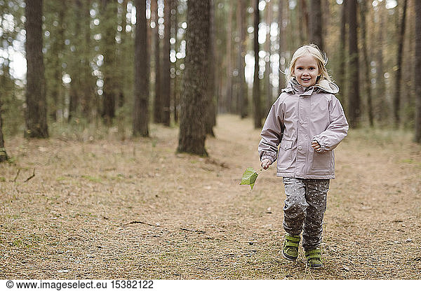 Portrait of smiling little girl in the woods