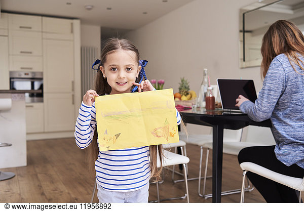 Portrait of smiling little girl showing drawing while her mother working on laptop in the background