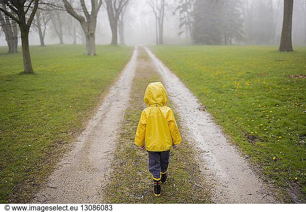 Rear view of boy in raincoat walking on dirt road during foggy weather, Rear view of boy in raincoat walking on dirt road during foggy weather