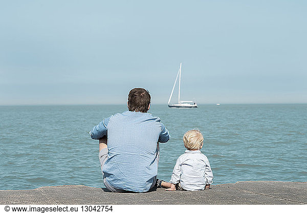 Rear view of father with son sitting at beach against blue sky during sunny day, Rear view of father with son sitting at beach against blue sky during sunny day