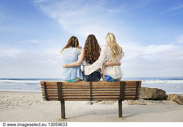 Rear view of friends sitting on bench at beach, Rear view of friends sitting on bench at beach