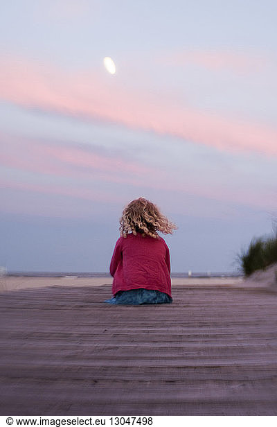 Rear view of girl sitting at beach against sky during sunset