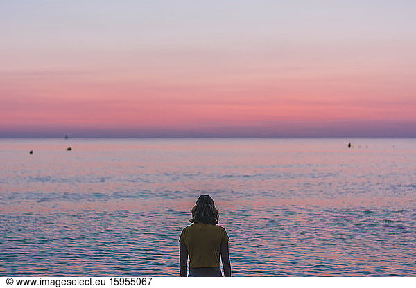 Rear view of teenage girl looking at horizon over sea during sunrise