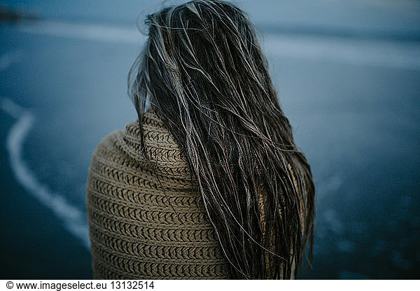 Rear view of wet woman with scarf standing at beach at dusk, Rear view of wet woman with scarf standing at beach at dusk