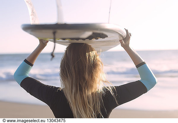 Rear view of woman carrying surfboard on head while standing at beach, Rear view of woman carrying surfboard on head while standing at beach