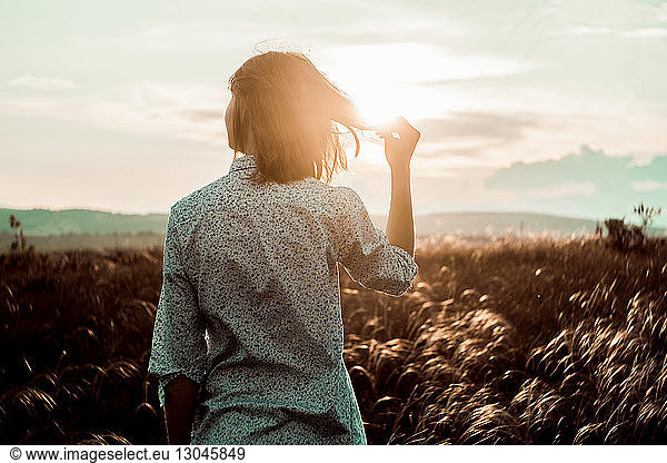Rear view of woman holding hair while standing on field against sky during sunset, Rear view of woman holding hair while standing on field against sky during sunset