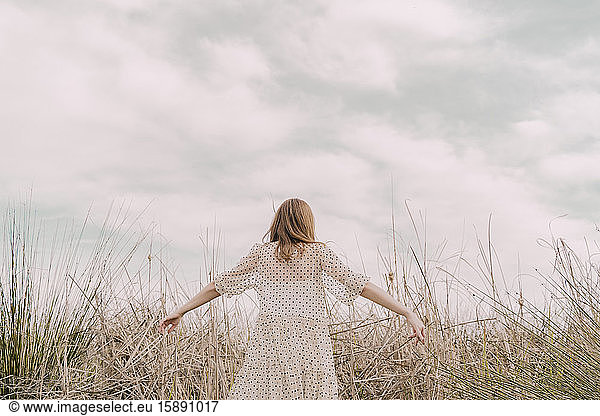 Rear view of woman in vintage dress with outstretched arms at a remote field in the countryside, Rear view of woman in vintage dress with outstretched arms at a remote field in the countryside