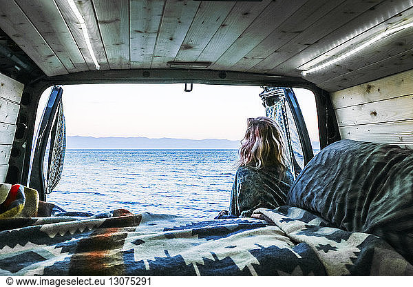Rear view of woman looking at sea while leaning against travel trailer, Rear view of woman looking at sea while leaning against travel trailer