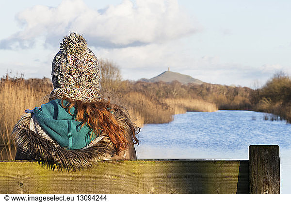 Rear view of woman sitting on bench at riverbank during winter, Rear view of woman sitting on bench at riverbank during winter