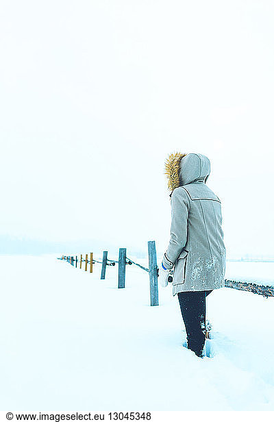 Rear view of woman standing by railing on snow covered field, Rear view of woman standing by railing on snow covered field