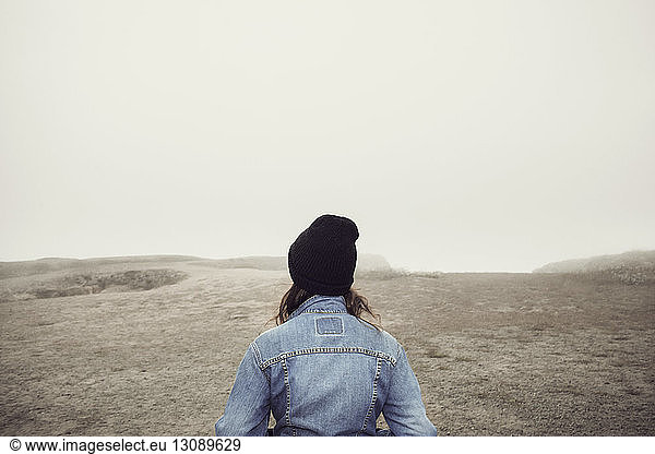 Rear view of woman standing on cliff against clear sky