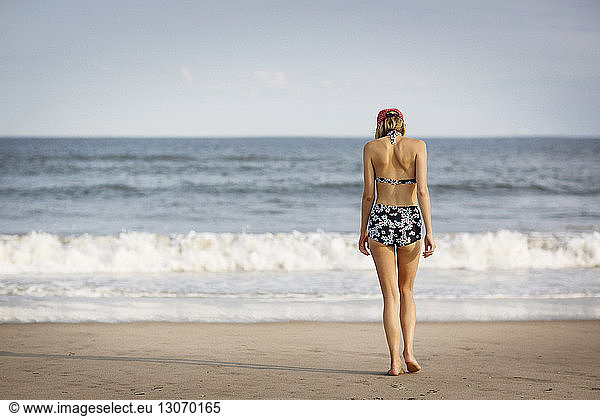 Rear view of woman walking on shore at beach, Rear view of woman walking on shore at beach