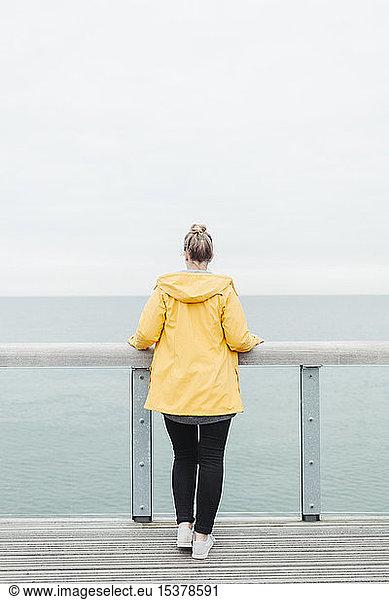 Rear view of young woman wearing yellow rain coat, Rear view of young woman wearing yellow rain coat