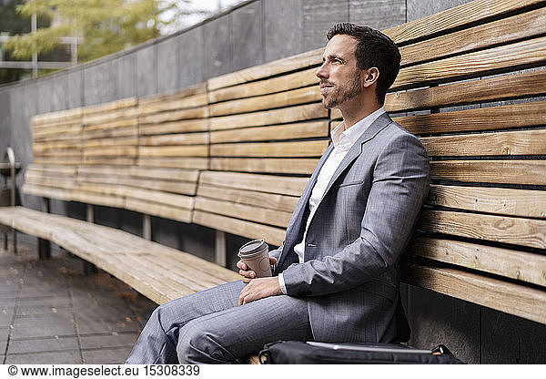 Relaxed businessman sitting on wooden bench in the city