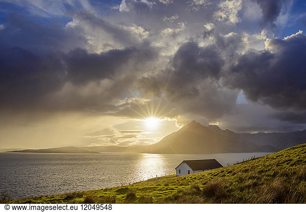 Rooftop of a house along the Scottish coast with sun shining through the clouds over Loch Scavaig,  Isle of Skye in Scotland