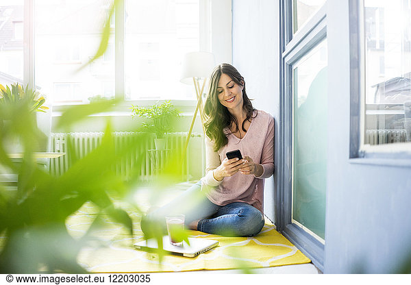Smiling woman sitting on floor using cell phone