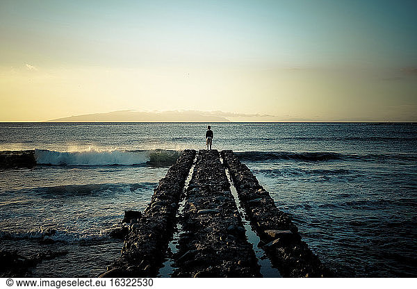 Spain,  Canary Islands,  Tenerife,  back view of child standing at pier looking at the sea, Spain,  Canary Islands,  Tenerife,  back view of child standing at pier looking at the sea