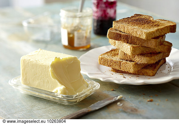 Stack of Whole Wheat Toast on Plate with Block of Butter and Jam on Tabletop