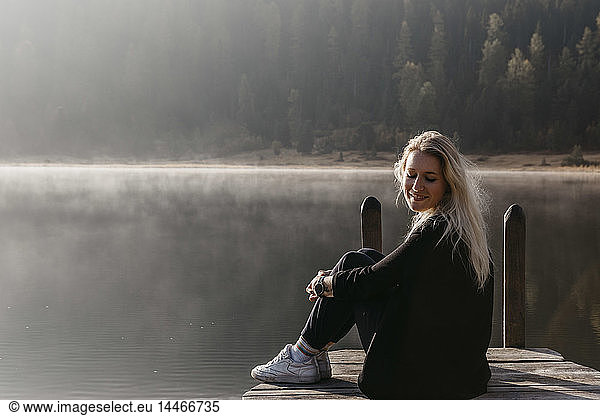 Switzerland,  Engadine,  Lake Staz,  smiling young woman sitting on a jetty at lakeside in morning sun
