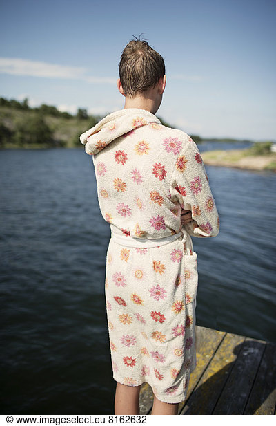 Teenage boy in bathrobe looking at lake, Teenage boy in bathrobe looking at lake