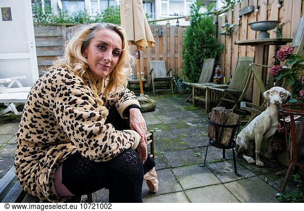 The hague,  Netherlands. Elder blonde female in her coat with tiger print sitting on a small bench in her private backyard garden.