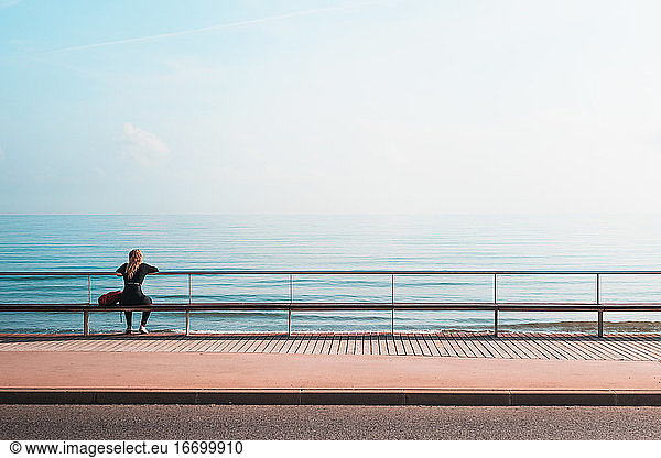 View From Behind To A Blonde Woman Sitting In Front Of The Sea, View From Behind To A Blonde Woman Sitting In Front Of The Sea