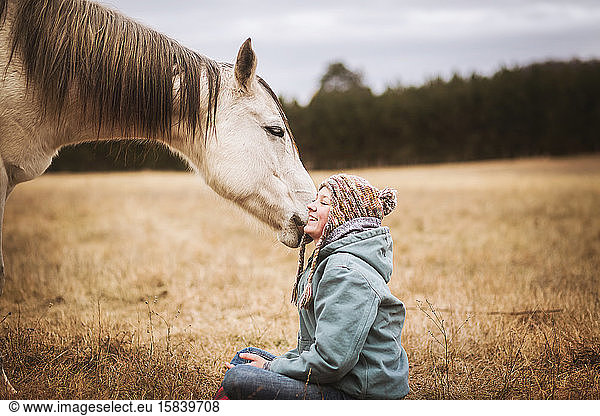 white horse tugging on girls hat in field in the fall while girl sits