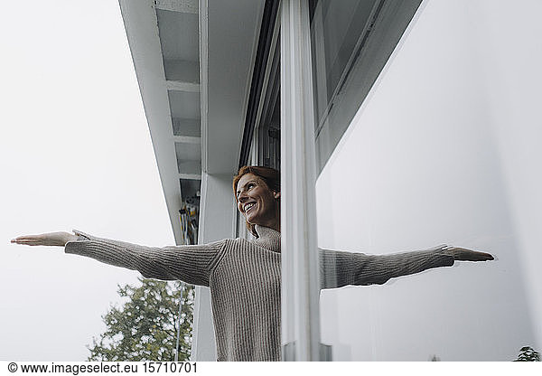 Woman checking weather,  holding hand out of window