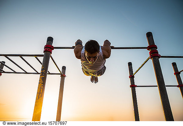 Young man practicing calisthenics at an outdoor gym at sunrise